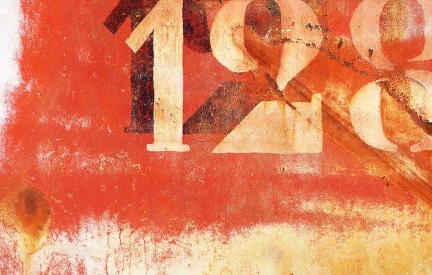 De oude roestige geschilderde achtergrond van de metaalmuur met aantallen