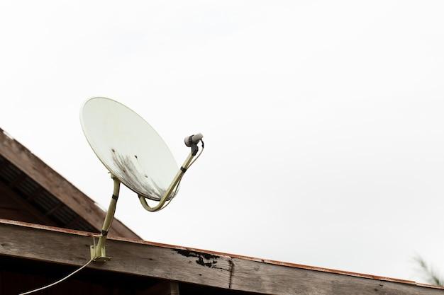 De oude satellietschotels op houten huisdak