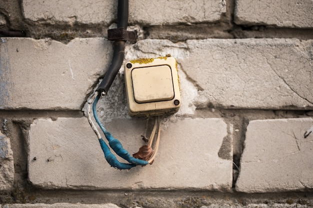 De oude schakelaar op de bakstenen muur verdraaide de blauwe tape.