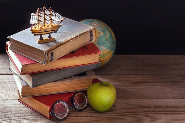 De oude schoolboeken, schoolboeken en schoolspullen liggen op een houten tafel.