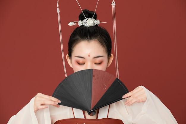 De oude schoonheid van hanfu bedekte het gezicht met een waaier