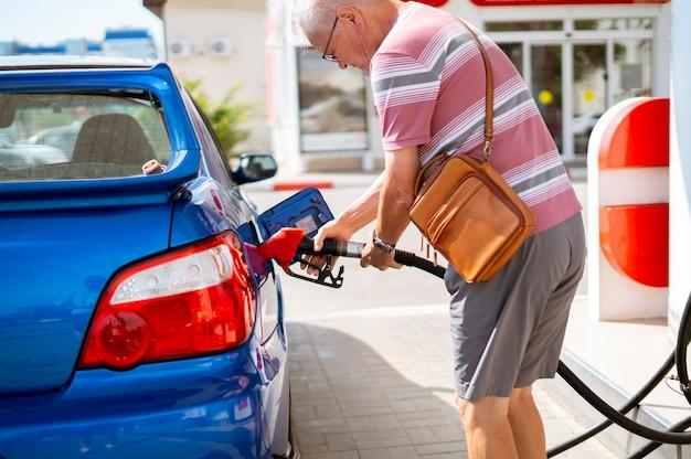 De oude senior man vult zijn auto met benzine bij het tankstation, toeristen reizen