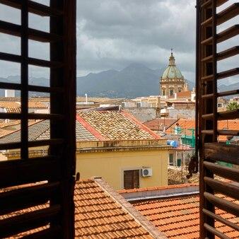 De oude stad palermo door het open raam met houten luiken, sicilië, italië