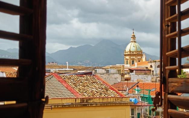 De oude stad palermo op sicilië door het open raam met luiken, italië