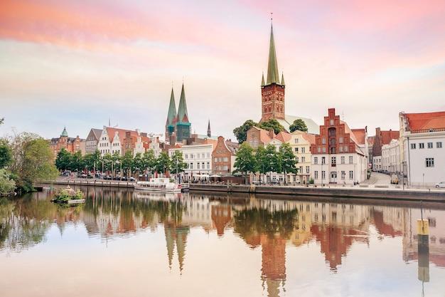 De oude stad van lübeck die in trave-rivier, duitsland wordt weerspiegeld