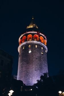 De oude toren van oriëntatiepuntgalata die door lichten in de avond wordt verlicht