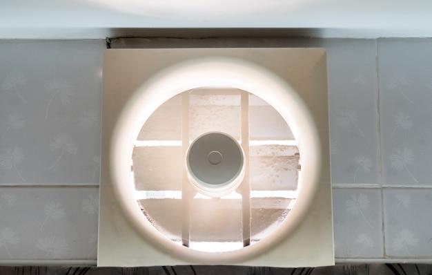 De oude ventilator werkt aan de muur boven de keukendeur om voedselgeuren te absorberen tijdens het koken in de keuken, vooraanzicht voor de kopieerruimte.