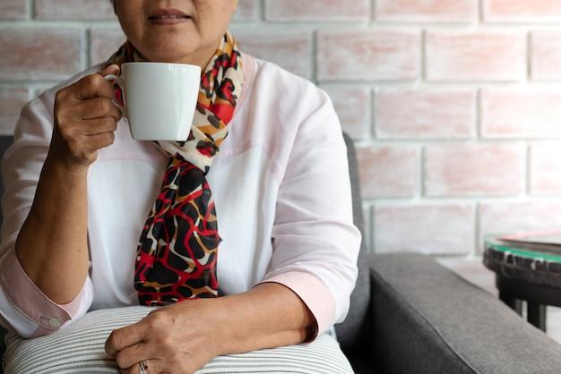 De oude vrouw houdt thuis een kop van hete koffiedrank