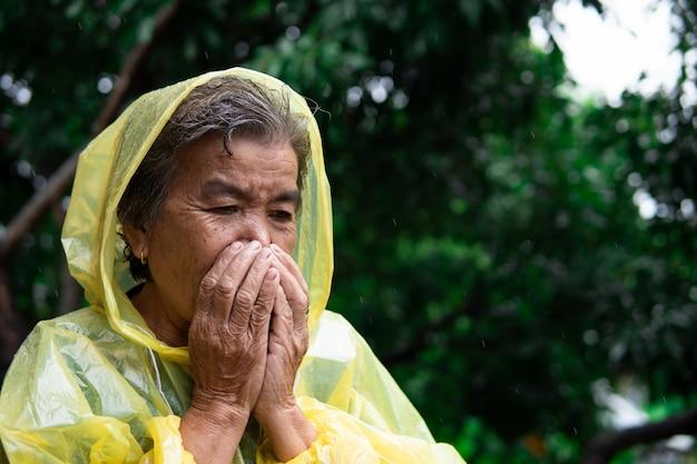 De oude vrouw in regenjas hoesten tijdens de regenval.