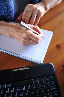 De oude vrouw werkt met computer
