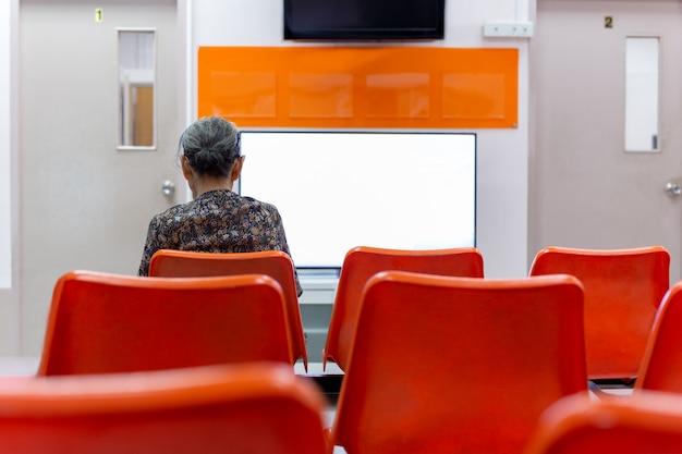 De oude vrouw zit op oranje stoel wachtend op gezondheidsdiensten in het ziekenhuis.