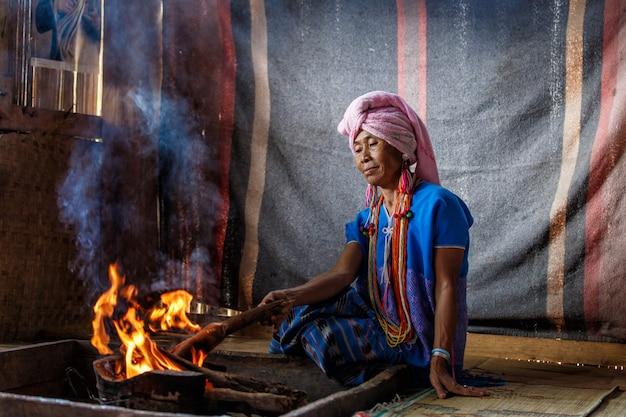 De oude vrouwelijke stam van de karenheuvel kookt traditioneel