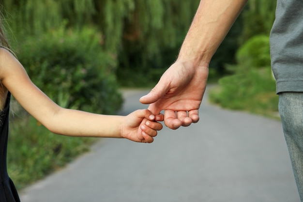 De ouder die de hand van het kind met een gelukkig houdt