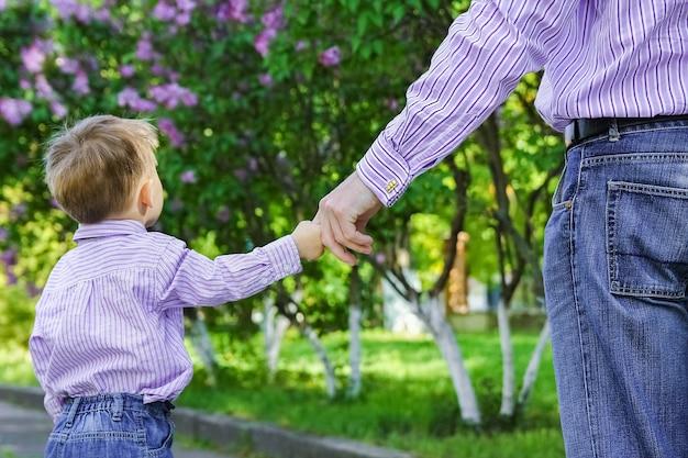 De ouder die de hand van het kind vasthoudt met een vrolijke achtergrond