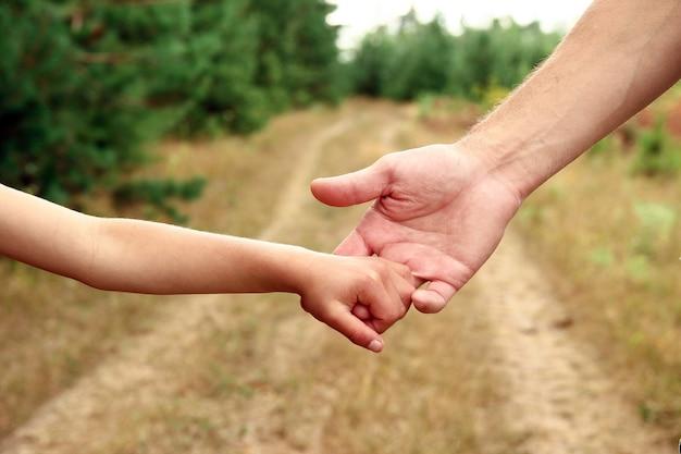 De ouder houdt de hand van een klein kind in de buurt van de weg vast