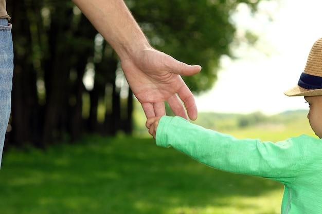 De ouder houdt de hand van een klein kind in de natuur vast