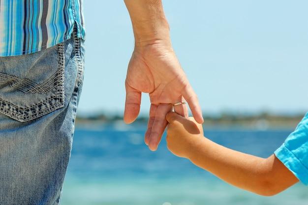 De ouder houdt de hand van een klein kind op zee vast