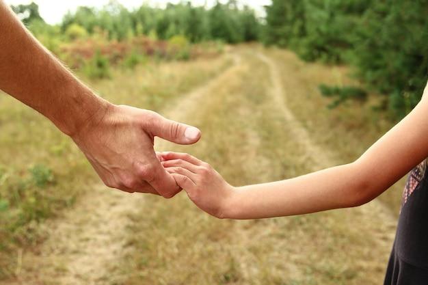 De ouder houdt de hand van een klein kind vast in de buurt van het pad