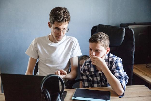De oudere broer helpt de jongere thuis bij het leren op afstand. tieners zitten aan een tafel met een laptop, tablet en koptelefoon.