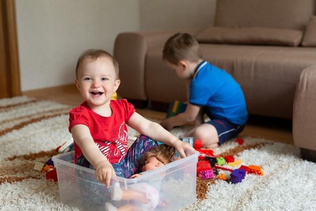 De oudere broer speelt op het tapijt met de constructeur, en de zus zit in een kist onder de constructeur vandaan.