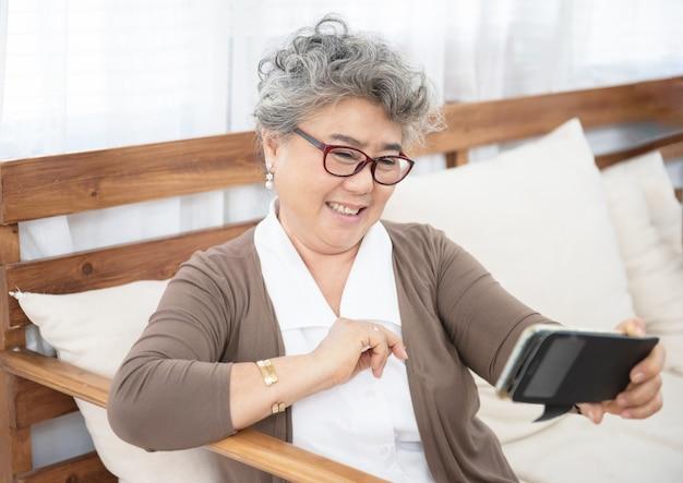 De oudere grootmoeder die telefoon met behulp van maakt thuis selfie