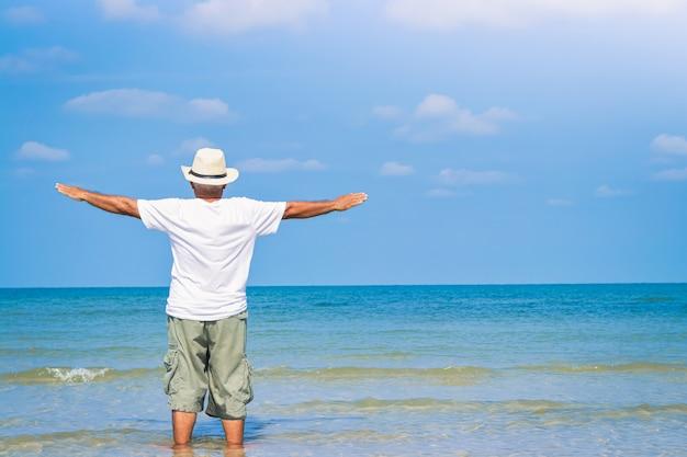 De oudere man droeg een hoed, keerde zijn rug toe en liet hem met vreugde zijn handen opheffen om naar de zee te komen.