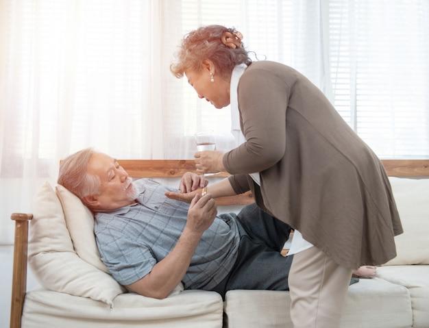 De oudere man neemt pillen terwijl de oudere vrouw zorgt