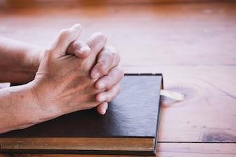 De oudere vrouw bidt met een heilige bijbel