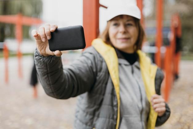 De oudere vrouw die van smiley een selfie buitenshuis neemt tijdens het trainen