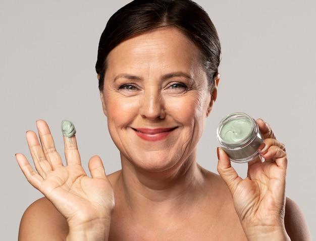De oudere vrouw die van smiley gezichtsmasker gebruikt