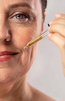 De oudere vrouw die van smiley serum gebruikt voor haar mondrimpels
