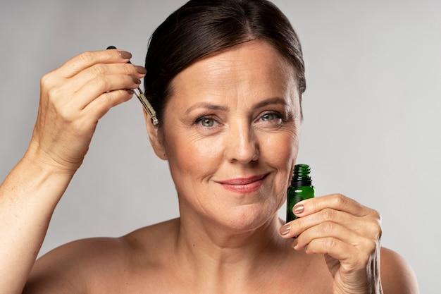 De oudere vrouw die van smiley serum op haar gezicht gebruikt