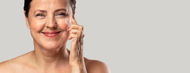 De oudere vrouw die van smiley vochtinbrengende crème op haar gezicht gebruikt