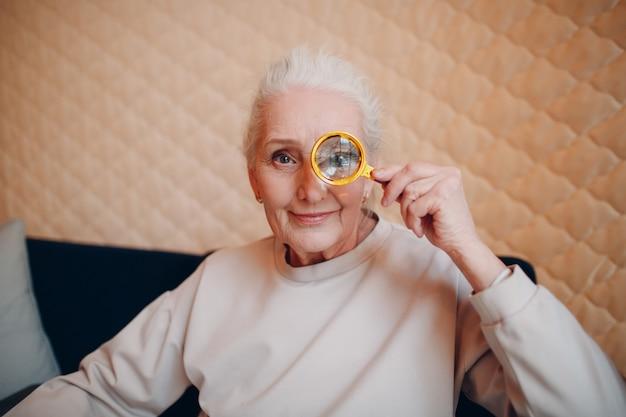 De oudere vrouw met vergrootglas in de hand