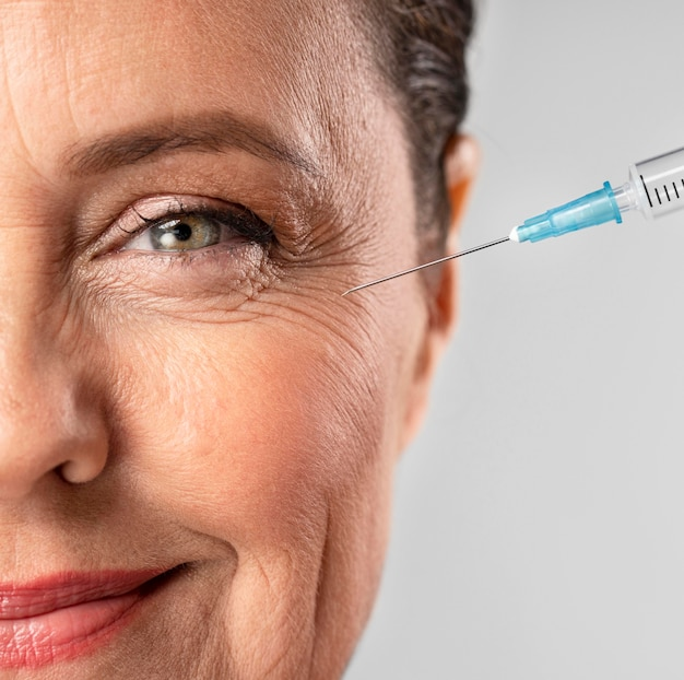 De oudere vrouw van smiley die injectie voor haar oogrimpels gebruikt