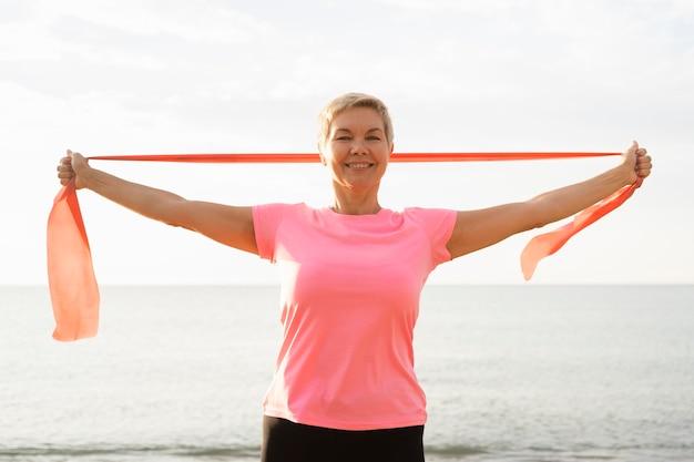 De oudere vrouw van smiley met elastisch koord op het strand