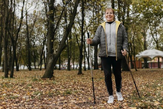 De oudere vrouw van smiley met wandelstokken en exemplaarruimte