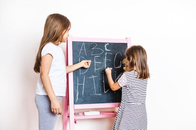 De oudere zus geeft les aan de jongere op een krijtbord