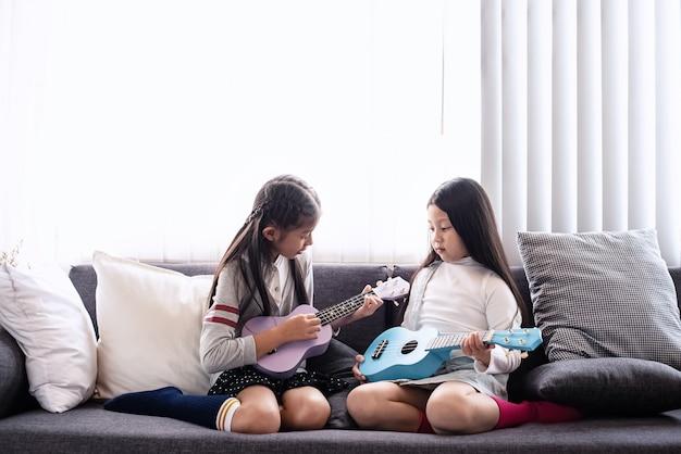 De oudere zus geeft les aan de jongere zus voor het spelen van ukelele, met geïnteresseerd gevoel, in de woonkamer, samen lerend, wazig licht rond