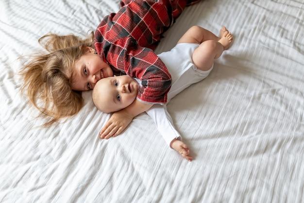 De oudere zus knuffelt de jongere baby thuis op bed