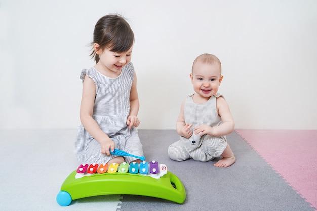 De oudere zus leert de jongere om met speelgoed te spelen. vroege ontwikkeling van kleuters.