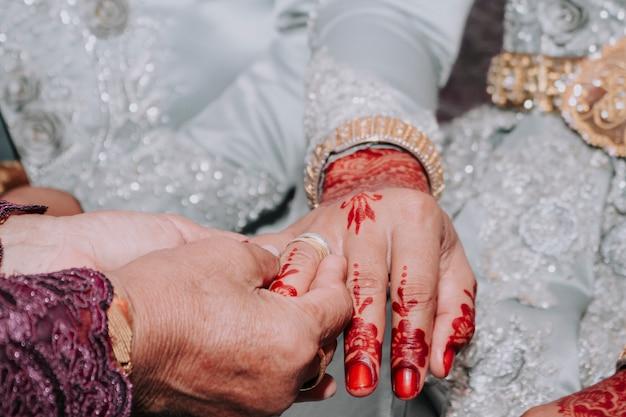 De ouders van de bruidegom zetten een ring om de vinger van de bruid