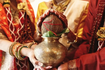 De ouders van de Indiase bruid houden een schaal met kokosnoot onder haar handen