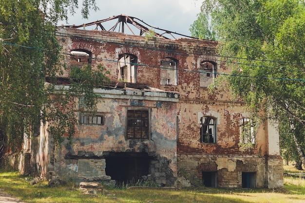 De overblijfselen van een vervallen verlaten stenen huis bedekt met mos en begroeid met bomen in een bos