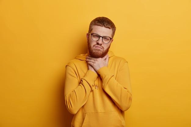 De overstuur jonge man heeft kort rood haar en korte haren, raakt de nek aan en lijdt aan keelpijn, heeft een pijnlijk gevoel tijdens het slikken, draagt een hoodie, geïsoleerd over een gele muur. slecht symptoom