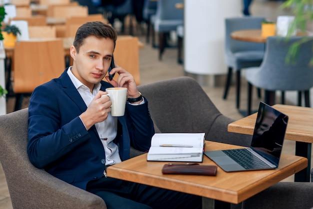 De overwerkte zakenman heeft koffiepauze en het spreken op smartphone