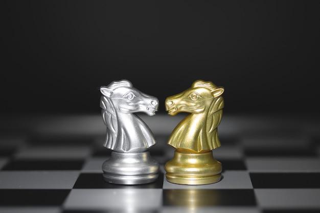 De paardenschaakstukken vechten, gouden en zilveren paardenschaken op een schaakbord. leider bedrijfsconcept