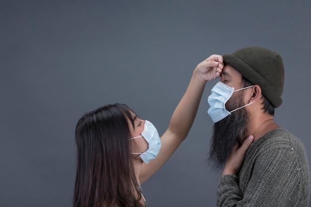 De paarliefde draagt masker terwijl zorg samen van zieken op grijze muur.