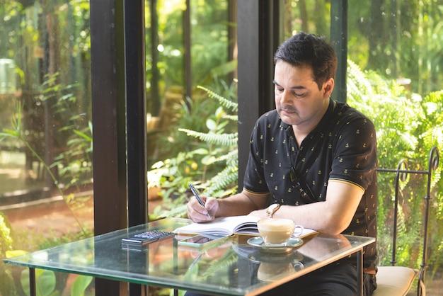 De pakistaanse bedrijfs aziatische mens in het toevallige toevallig dragen schrijft op notitieboekje gebruikend slimme mobiele telefoon met kop van koffie in koffie, freelance bedrijfsconcept.
