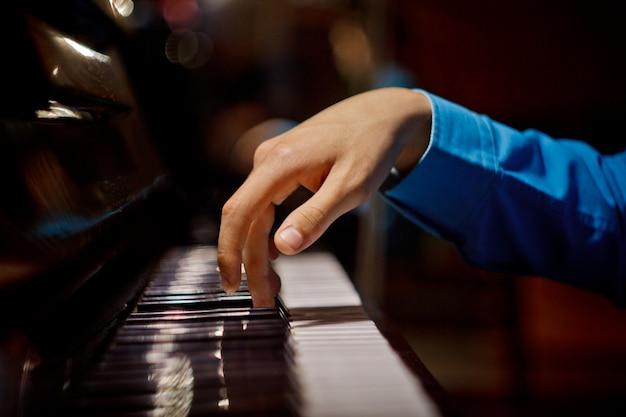 De palm ligt op de toetsen en speelt het toetsenbordinstrument in de muziekschool.